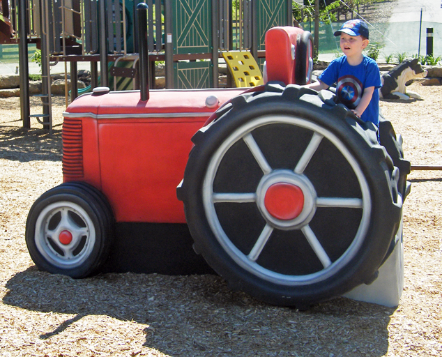Kid sitting on tractor in Showman's Circle Farm-themed play area at Lake Metroparks Farmpark